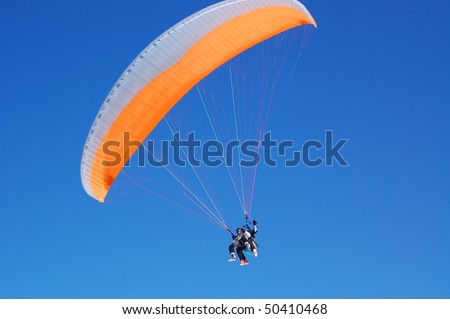 Paragliders turning in blue sky