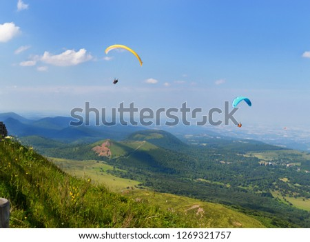 Paragliders who fly in the middle of landscape volcanoes and mountains. #1269321757