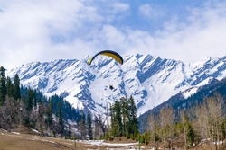 Paragliding at Solang Valley with Snow cladded mountains of Dhauladhar in background en-route to Rohtang Pass, Manali, Himachal Pradesh, India.