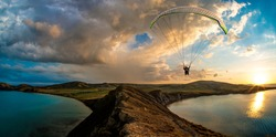 Paragliding concept, paraglider pilot fly in sky on beauty nature mountain and sea coast landscape Crimea background, horizontal photo