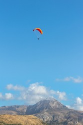 Paragliding in an orange paraglider against a clear blue sky in a bright summer's day in Crete, Greece. Hills and mountain with small clouds in the background.