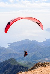 Paragliding in sky. Paraglider tandem flying over the sea and mountains. Extreme sport
