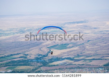 Paragliding in tandem over Tian Shan mountains near Almaty.  The green Ush Konir plato with juice meadows covered by clouds after  the rain. Best place for extreme activity in in Kazakhstan.