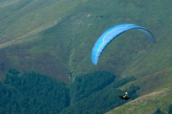 Paragliding in the Carpathian Mountains in Ukraine. Paraglider fly over a mountain valley in summer sunny day.