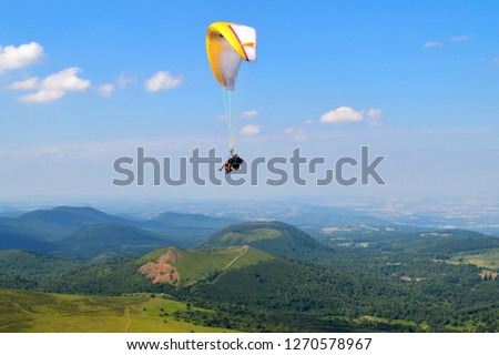 Paragliding in the middle of Auvergne volcanoes mountains #1270578967