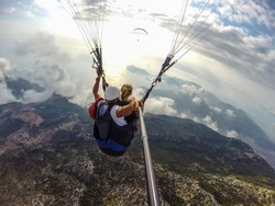 Paragliding in the sky. Paraglider tandem flying over mountains in bright sunny day. Aerial view of paraglider and Blue Lagoon in Oludeniz, Turkey. Extreme sport. Landscape