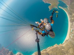 Paragliding in the sky. Paraglider tandem flying over the sea with blue water and mountains in bright sunny day. Aerial view of paraglider and Blue Lagoon in Oludeniz, Turkey. Extreme sport. Landscape