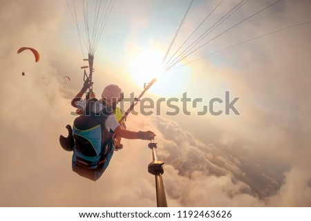 Paragliding in the sky. Paraglider tandem flying over the sea with blue water and mountains in bright sunny day. Aerial view of paraglider and Blue Lagoon in Oludeniz, Turkey. Extreme sport. Landscape #1192463626