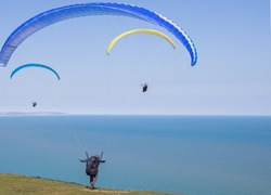 Paragliding man taking off from edge of cliff.