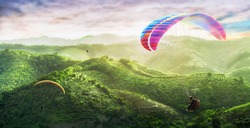 Paragliding multicolor. Paraglider flying over Landscape from the background Beauty nature mountain landscape of the sky. Paragliding Sports. Concept of extreme sport, taking adventure challenge.