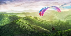 Paragliding multicolor. Paraglider flying over Landscape from the background Beauty nature mountain landscape of the sky. Paragliding Sports. Concept of extreme sport, taking adventure, challenge.