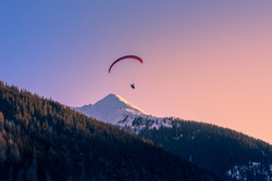 Paragliding over mountain peak in the alps