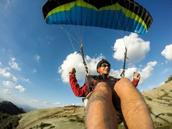 paragliding pilot smiling in blue sky day