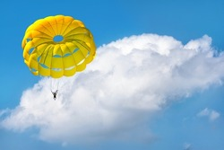 Paragliding using a parachute on background of blue cloudy sky.