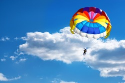 Paragliding using a parachute on the background of cloudy blue sky.