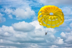 Paragliding using a yellow parachute on background of blue cloudy sky.