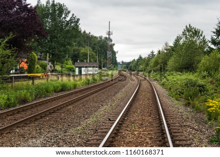 Parallel Curving Railway Tracks through the Countryside on a Cloudy Summer Day. Fort Langley, BC, Canada. #1160168371