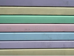 Parallel planks of wood painted a variety of pastel shades of colour. Green, yellow, pink, sky blue, lilac and mauve