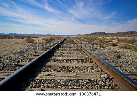 Parallel rails lead off into the vast open distances of the Mojave Desert.