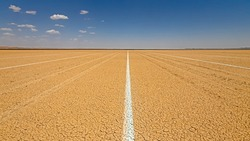 Parallel white lines painted on clay surface of Hakskeen salt pan, Northern Cape, South Africa