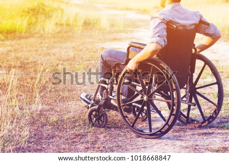Paralyzed man using Wheelchair outdoor