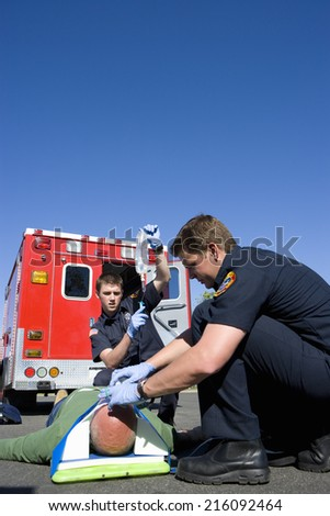 Paramedic and colleague helping man on stretcher by ambulance, low angle view