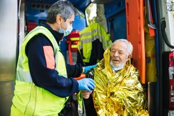 Paramedic rescues an elderly person in distress with an ambulance by covering him with a thermal blanket and making him drink a hot drink - Concept of first aid