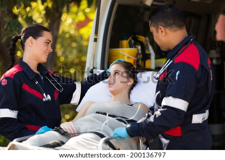paramedic team talking to young patient before she going into an ambulance