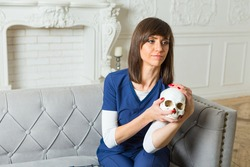 paramedic wearing blue medical scrubs sits on a lounge with cranium in her hands