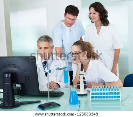 Paramedical or technical staff grouped together looking at a computer in a laboratory