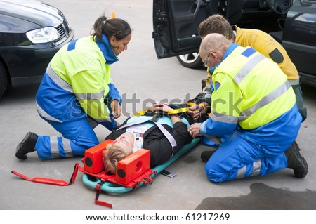 Paramedics and a fireman strapping a wounded woman  with a neck brace on a stretcher - stock photo