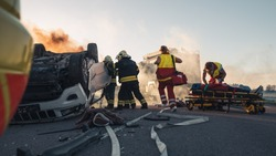Paramedics and Firefighters Arrive On the Car Crash Traffic Accident Scene. Professionals Rescue Injured Victim Trapped in Rollover Vehicle by Extricating Them, giving First Aid and Extinguishing Fire