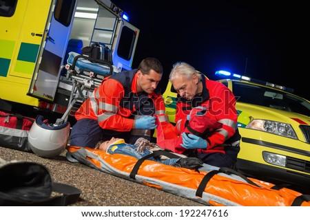 Paramedics giving first-aid to injured motorbike woman driver at night