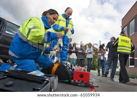 Paramedics tending to the first aid of an injured woman on a stretcher at the scene of a car crash, whilst a police woman is escorting a bystander towards the cordon tape, being filmed by a camera man - stock photo