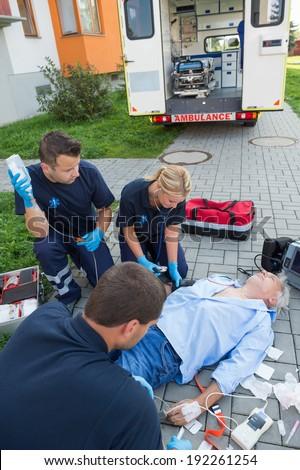 Paramedics treating injured senior man lying on street