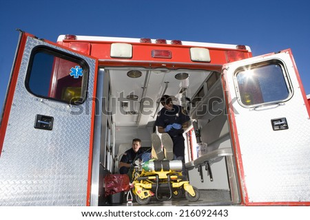 Paramedics with man on stretcher in ambulance, low angle view