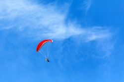 Paramotor flying in a blue sky. Adventure man active extreme sport pilot flying in sky with paramotor engine glider parachute