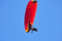 Paramotor flying in the blue sky background.