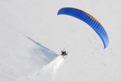 Paramotor seen from the sky in winter flying at low altitude and leaving a trail in virgin snow