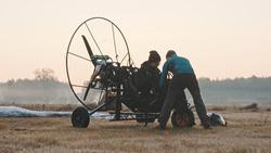 Paramotorgliding. two men preparing for the tandem paramotorgliding.