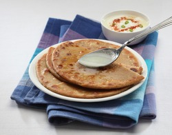 Parantha (indian bread) with desi ghee spoon.