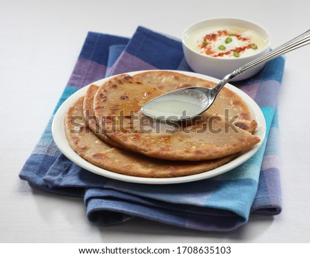 Parantha (indian bread) with desi ghee spoon. Photo stock ©