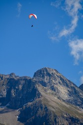 Paraplaners in tandem gliding in blue sky with view on Alpine mountains on paraplane