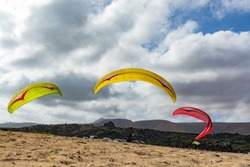 Paraplaners with paraplanes trying to take off, on sandy beach, extreme sport