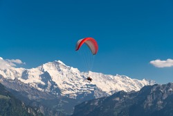 Paraplanes fly over beautiful Interlaken valley and lakes Brienz and Thun, Harder Kulm, Switzerland