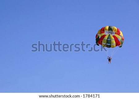 Parasailing against clear blue sky