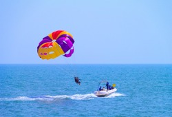 Parasailing at Candolim Beach in Goa - Indian extreme Sport. Tourists parasailing - popular entertainment for holiday travelers on Candolim Beach in Goa, India.