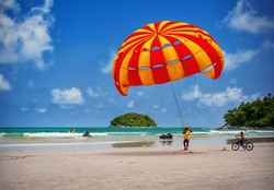 Parasailing extreme sports on beach in blue sky background