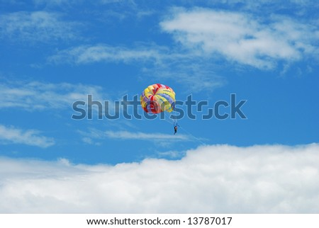 Parasailing in blue cloudy sky