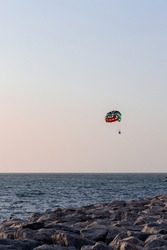Parasailing in Dubai - single colorful parasail (parachute) tendem wing flying, towed behind a boat before sunset with orange and blue sky background. Copy space, portrait view.